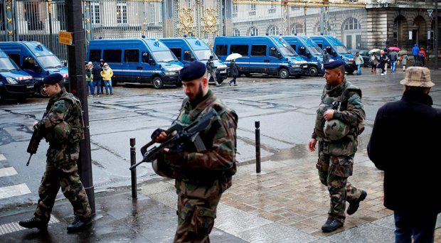 French soldiers patrol outside the Paris hall of Justice, Wednesday, March 30, 2016 while Frenchman Reda Kriket is being questioned by a magistrate