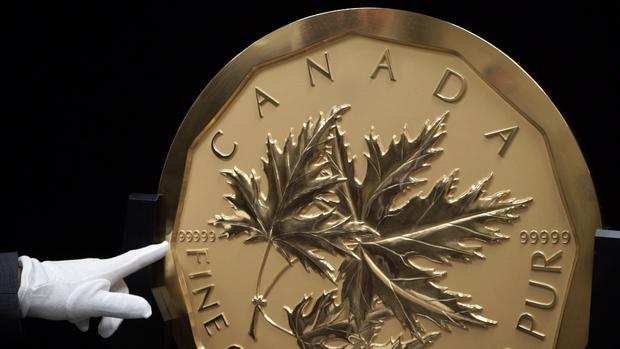 A hand carved Canadian maple leaf adorns one side of the coin.