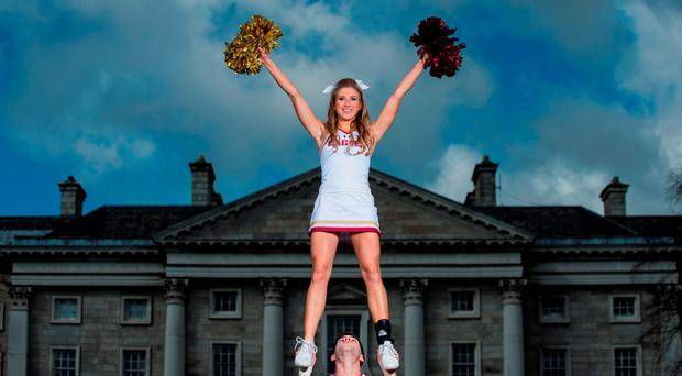 Boston College cheerleader Elizabeth Pehota is lifted by her team-mate Matthew Keemon at the unveiling of Trinity College as the Welcome Village for the Aer Lingus College Football Classic (SPORTSFILE)