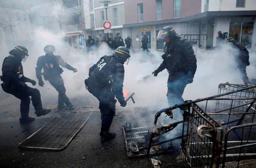 French gendarmes clean debris after youths set fire to garbage bins and caddies as French high school and university students attend a demonstration against the French labour law proposal in Nantes. Photo: Reuters