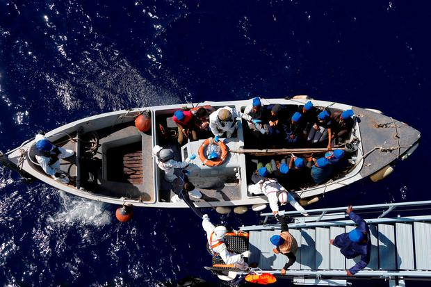 In this March 29, 2016 picture migrants get help by Italian sailors to transfer from the German combat supply ship 'Frankfurt am Main' to the their ship 'Grecale' after being rescued during EUNAVFOR MED Operation Sophia in the Mediterranean Sea off the coast of Libya. Photo: AP