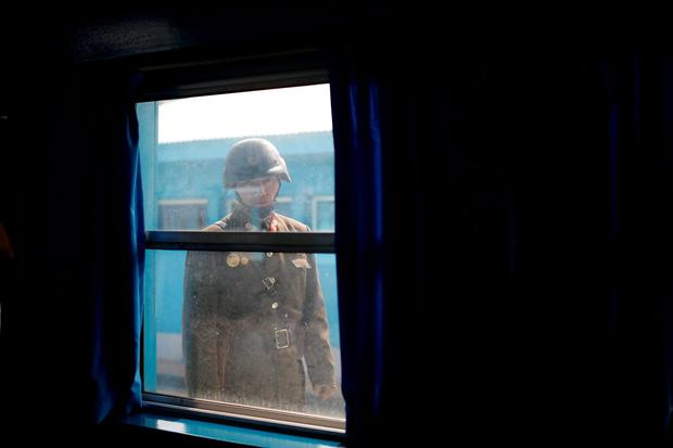 A North Korean soldier looks inside a conference room in the United Nations Command Military Armistice Commission Conference Building at the truce village of Panmunjom, South Korea, March 30, 2016. REUTERS/Kim Hong-Ji