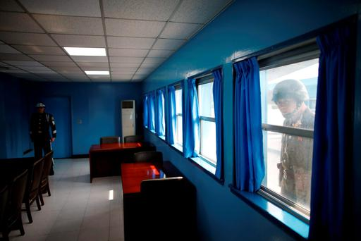 A North Korean soldier peeps into a conference room in the United Nations Command Military Armistice Commission Conference Building as a South Korean soldier stands guard, at the truce village of Panmunjom, South Korea, March 30, 2016. REUTERS/Kim Hong-Ji