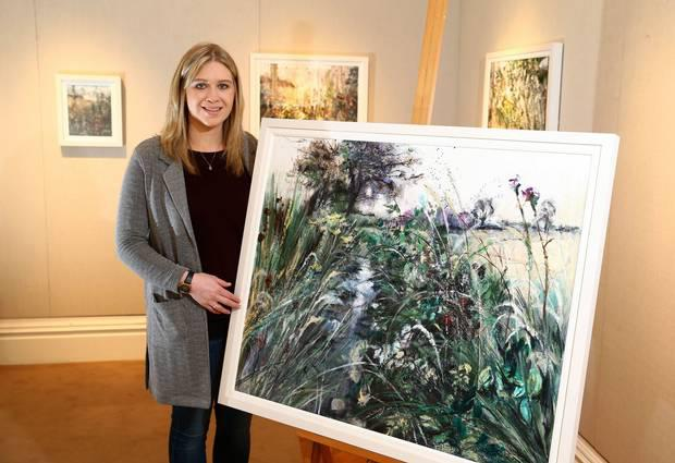 Emma Spence with one of her paintings inspired by the landscape of her Magheraconluce home