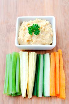 Healthy chickpea dip with colourful raw vegetable sticks