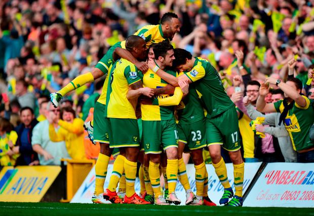 Martin Olsson (2nd R) of Norwich City celebrates scoring his team's third goal with his team mates
