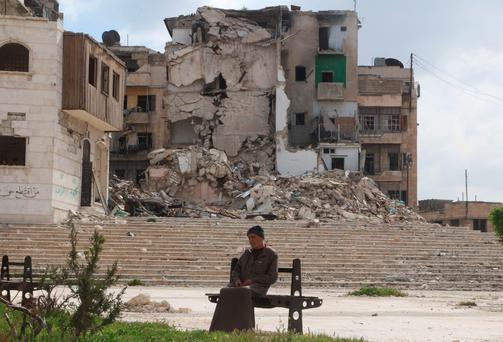 A man sits in front of a damaged building in a rebel held area of Aleppo, Syria March 27, 2016. Reuters/Abdalrhman Ismail