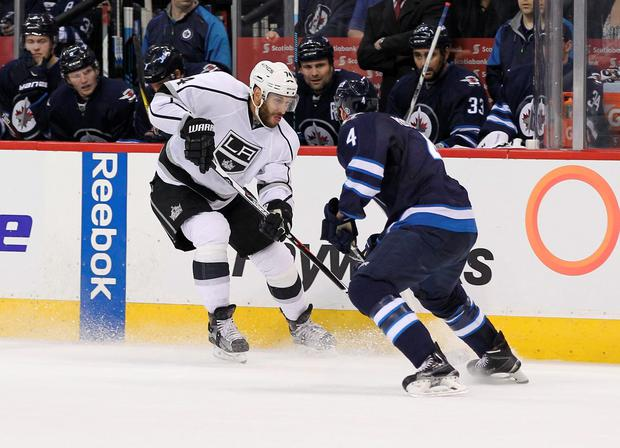 Los Angeles Kings forward Dwight King (74) tries to get past Winnipeg Jets defenseman Paul Postma (4) during the NHL hockey game at MTS Centre. Photo: Ray Peters-USA TODAY Sports