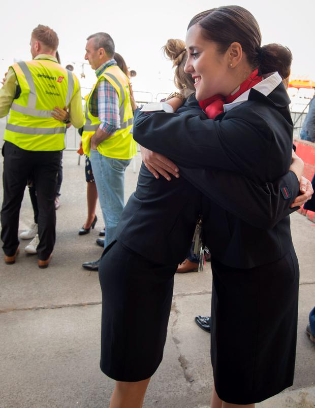 Brussels Airport staff hug as the first plane takes off from Brussels Airport, which partially re-opened following a bomb blast 12 days ago, in Zaventem, Belgium. Reuters/Benoit Doppagne/Pool