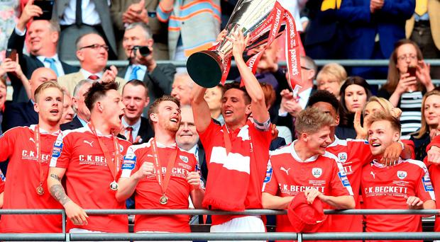 Barnsley's Conor Hourihane lifts the Johnstone's Paint Trophy at Wembley Stadium, London