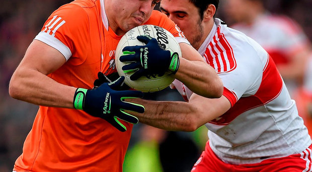 Armagh's Stefan Campbell is tackled by Derry defender Chrissy McKaigue Photo: Oliver McVeigh / SPORTSFILE