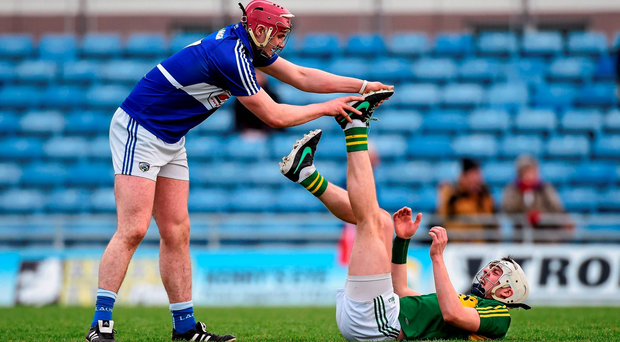 Ryan Mullaney of Laois shows his sportsmanship by coming to the aid of Kerry's Shane Nolan after he went down with cramp. Photo: Sportsfile