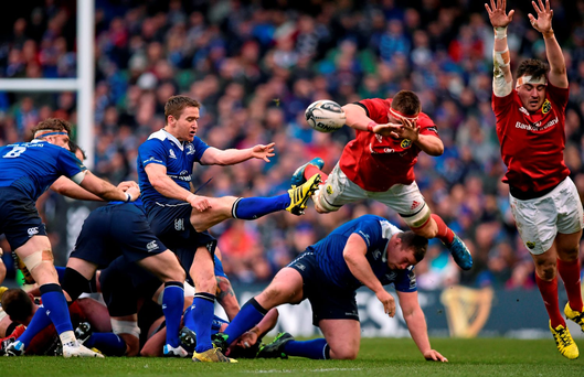 Eoin Reddan gets his kick away despite the efforts of CJ Stander and Niall Scannell Photo: Brendan Moran / SPORTSFILE