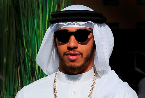 Mercedes driver Lewis Hamilton of Britain walks out of the Mercedes lounge as he wears the traditional Arab robe ahead of the Bahrain Formula One Grand Prix. (AP Photo/Kamran Jebreili)