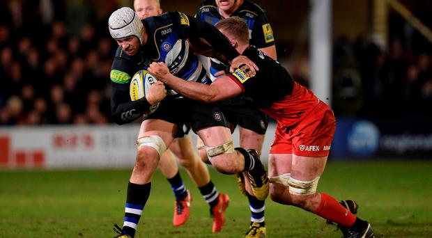 Bath Rugby's Dave Attwood is tackled by Saracens' George Kruis