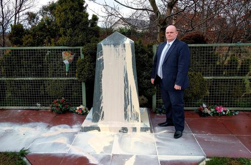 Ian McCrea standing next to a memorial to the victims of an IRA bomb in County Tyrone after it was vandalised Credit: DUP/PA Wire