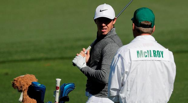 Rory McIlroy speaks to his caddie while on the driving range during a practice round for the Masters golf tournament