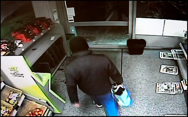 The armed raider calmly leaves Centra on Johnstown Road in Cabinteely with the shops takings in a plastic bag.