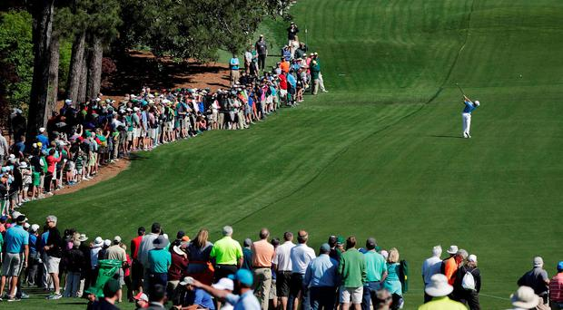 A large crowd follows Rory McIlroy as he hits from the eighth fairway during practice for the Masters. JAE C HONG/AP