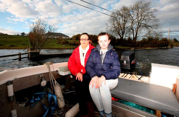 Caroline Collins and her daughter Amy (11) outside their home near Castleplunket, which is still cut off by flooding. Photo: Brian Farrell.