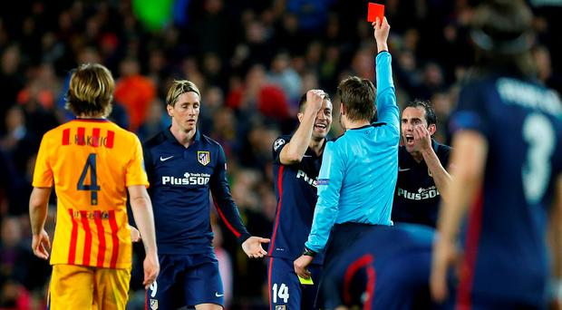 Atletico's Fernando Torres, 2nd left is shown a red card by Referee Felix Brych during a Champions League quarter-final, first leg soccer match between FC Barcelona and Atletico Madrid at the Camp Nou stadium