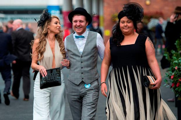 Racegoers attend the opening day of the Grand National Festival horse race meeting at Aintree Racecourse in Liverpool