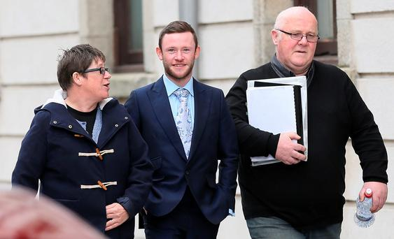 Devon Murray with his parents Fidelma and Michael after the opening day of a High Court action taken by agent Neil Brooks. Photo: Collins