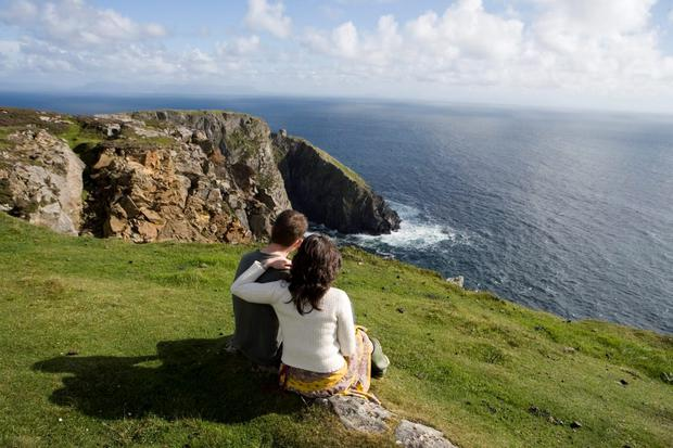 A couple looking at the Slieve League cliffs along the Wild Atlantic Way in Donegal.