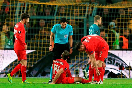 Liverpool's Jordan Henderson sits injured on the turf during the UEFA Europa League Quarter Final, First Leg match at Signal Iduna Park, Dortmund