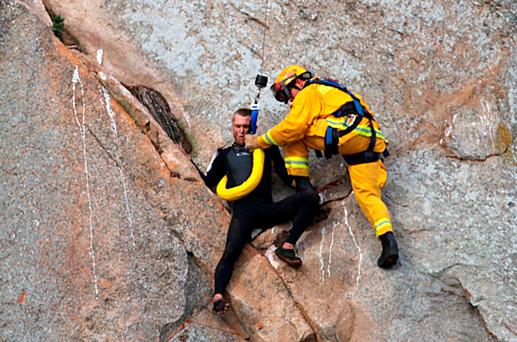 In this photo provided by Bob Isenberg, Michael Banks is stranded on a ledge some 80 feet off the ground on Morro Rock, a landmark in Morro Bay