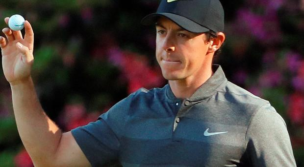 Rory McIlroy holds up his ball after an eagle on the 13th hole