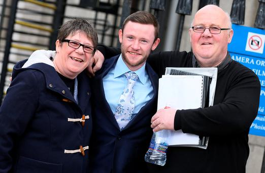 Devon Murray (centre) pictured with his parents Fidelma and Michael at the Four Courts Pic: Collins Courts