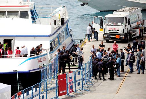 Migrants are escorted by police officers as they disembark from a ferry at a port in the Turkish coastal town of Dikili. Photo: Reuters