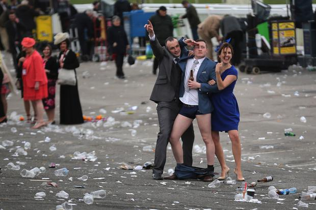 A man plays to the cameras as racegoers make their way home at the end of Ladies Day the second day of the Aintree Grand National Festival meeting on April 8, 2016 in Aintree, England.