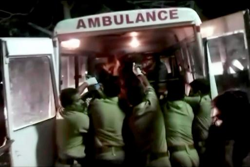 In this image made from video, officials put an injured person into an ambulance following a fire at a temple in Kollam, in the southern Indian state of Kerala, early Sunday, April 10, 2016. A number of people (Asianet News via AP Video)