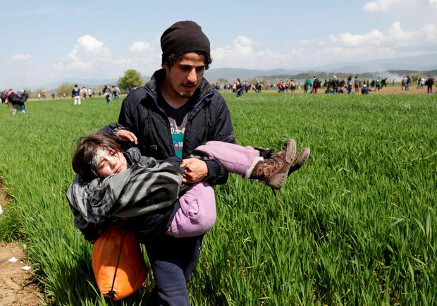 A migrant man carries his daughter during a protest at the northern Greek border point of Idomeni, Greece (AP Photo/Amel Emric)