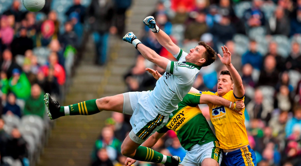 Kerry goalkeeper Brian Kelly punches the ball clear under pressure from Diarmuid Murtagh of Roscommon, and supported by Shane Enright. Photo: Sportsfile