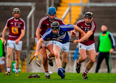 A 'bootless' PJ Scully of Laois attempts to gather possesssion, closely pursued by Wesmteath's Aonghus Clarke (left) and Tommy Gallagher, during Saturday's Division 1B relegation play-off at O'Connor Park. Photo: Sportsfile