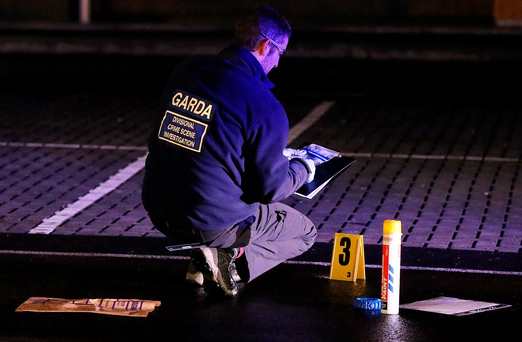 A forensic garda at the scene of the Finglas shooting on Friday Photo: Steve Humphreys
