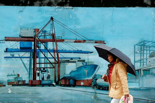 A woman walks a painting outside at Keelung port, northern Taiwan, in this March 20, 2016 file photo. REUTERS/Tyrone Siu/Files