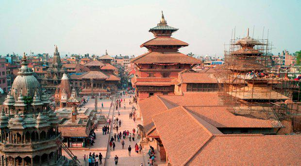 Nepalese workers restore a temple (R) in Durbar Square on April 10, 2016 in Patan, south of Kathmandu, as tourists and residents walk around the area that was damaged in last year's earthquake. File picture