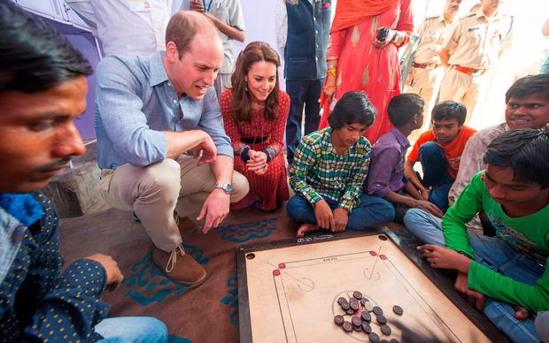 Catherine, Duchess of Cambridge and Prince William, Duke of Cambridge play a game of carrom with street children in New Dehli, India. (Photo by Dominic Lipinski - Pool/Getty Images)