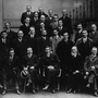 The Sinn Fein members elected in the December 1918 election at the first Dail Eireann meeting, called by Sinn Fein on January 21, 1919. Shown are (from l to r): 1st row: L. Ginell, Michael Collins (leader of the Irish Republican Army), Cathal Brugha, Arthur Griffiths (founder of Sinn Fein), Eamon de Valera (president of the Irish Republic), Count E. MacNeill, William Cosgrave and E. Blythe; 2nd row: P. Maloney, Terence McSwiney (Lord Mayor of Dublin), Richard Mulcahy, J. O'Doherty, J. O'Mahony, J. Dolan, J. McGuinness, P. O'Keefe, Michael Staines, McGrath, Dr. B. Cussack, L. de Roiste, W. Colivet and the Reverend Father Michael O'Flanagan (vice-president of Sinn Fein); 3rd row: P. War, A. McCabe, D. Fitzgerald, J. Sweeney, Dr. Hayes, C. Collins, P. O'Maillie, J. O'Mara, B. O'Higgins, J. Burke and Kevin O'Higgins; 4th row: J. McDonagh and J. McEntee; 5th row: P. B 1919 Ireland