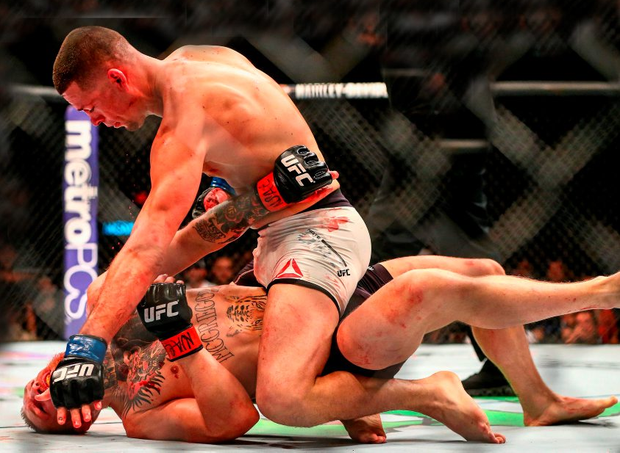 Conor McGregor takes some punishment from Nate Diaz during their welterweight bout at the MGM Grand Garden Arena, Las Vegas, Nevada. 'Once a man goes down to the floor in MMA, his opponent will then do his best to make sure he stays down – frequently through repeated use of elbow strikes to the head and face. It's this element of extreme brutality which both attracts and disgusts people.' Pic: Mark Rebilas/Sportsfile
