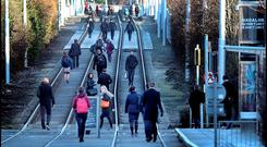 Commuters walk on the Luas line during one of the recent strikes, of which more are planned by drivers. Photo: Steve Humphreys