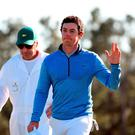 Rory McIlroy, with caddie JP Fitzgerald, salutes the Augusta crowd after finishing on the 18th green during the final round of the Masters (Getty Images)