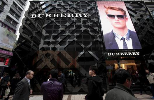 File photo of people walking outside a Burberry store in the Tsim Sha Tsui shopping district of Hong Kong, January 18, 2013. REUTERS/Bobby Yip/Files