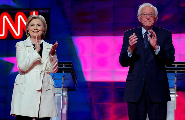 Democratic U.S. presidential candidates Hillary Clinton (L) and Senator Bernie Sanders applaud together before the start of a debate hosted by CNN and New York One at the Brooklyn Navy Yard in New York April 14, 2016