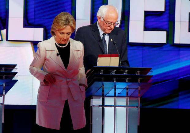 Democratic U.S. presidential candidate Hillary Clinton (L) and rival Bernie Sanders leave their podiums at the conclusion of the Democratic debate hosted by CNN and New York One at the Brooklyn Navy Yard in New York April 14, 2016