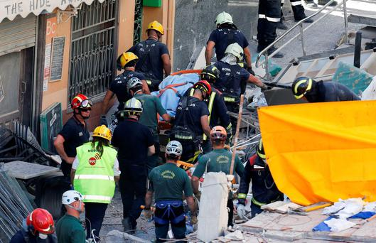 Firefighters and rescue workers carry the body of a victim from a collapsed building in Los Cristianos, in the Canary Island of Tenerife, Spain, April 14, 2016